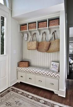 Mudroom off entryway with pale greige built-in storage bench with tongue and groove paneled backsplash topped with open storage cubbies. by marcy