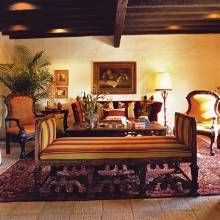 Furnishings enhance the Mexican Colonial ambience of the heavily beamed living room. Flooring is composed of hand-chipped cantera tiles from Mexico.