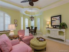 Sunny yellow tropical family room living room with red chairs - Grey Oaks, Naples, FL
