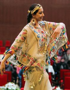 Iraqi Folk Dance, She wears a wide dress with colorful embroidery and accessorry