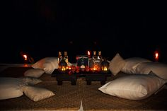 A custom Mezcal lounge lit by tiki torches in the sand and candles. Buzzworthy Events.
