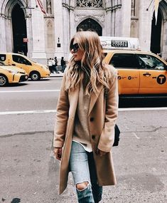 Tan coat over beige sweater, white shirt and pale blue jeans.