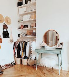 Closet with open shelves, hats on books, small teal vanity with round mirror and white fur covered stool