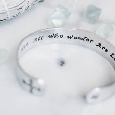 """This inspirational secret message bracelet is a great way to make a statement on your arm. The bracelet features a compass and crossed arrows on the ends, and the quote by J. Tolkien, """"Not All Who Wander Are Lost,"""" on the inside. Wire Jewelry, Jewelery, Hand Gestempelt, Crossed Arrows, Bracelet Quotes, Beads And Wire, Bracelet Making, Hand Stamped, Wedding Rings"""