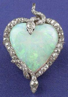Edwardian Platinum, Opal, and Diamond Snake Pendant/Brooch, designed as a heart-shaped opal entwined by two old mine and old European-cut diamond serpents.. via Skinner, Inc