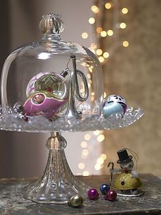 Under glass: cloche over a crystal cake dish and ornaments..very pretty