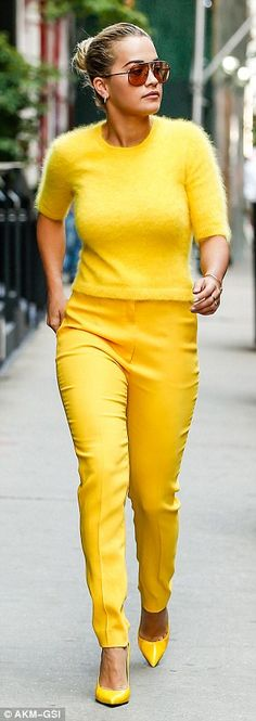 Not so mellow in yellow: The singer's ensemble featured a fuzzy knit jumper over matching high-waist trousers
