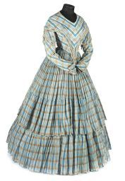 1840s one piece gown, the fabric sky blue and tan check, the dropped shoulders and deep pointed bodice embellished with cream silk fringe, the full skirts tiered