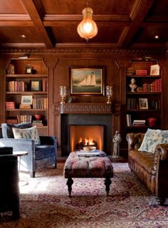 Nice mix of leather and upholstered pieces, beautiful wood, bookcases flanking the fireplace, rug