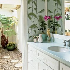 Coastal courtyard bath  In the master bath, the homeowners tore out everything and started over, with Palm Leaves wallpaper by Cole & Son and sturdy Corian countertops in Seaglass. The room opens to a courtyard garden.