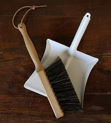 A small handbroom and dustpan set. Perfect for children or for cleaning small messes on your desk or tabletop.   Dustpan is white powder-coated steel, and handbroom is a oiled beechwood with horsehair bristles and a leather loop for hanging.