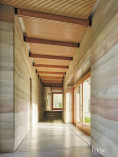 Hallways with thick earth-rammed walls and concrete floors - Modern Northern California Tree Ranch House | LuxeSource | Luxe Magazine - The Luxury Home Redefined