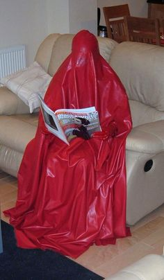 Reading in red rubber burqa