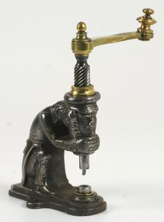 """Figural Leatherworker's Rivet Press - Cast & Wrought Iron and Brass. The Figure is a Bearded Man in a Cap and Tail Coat, Holding his Chin in his Hands. France. Circa 19th Century. 5-1/2"""". Truly Incredible Tool!!!!"""