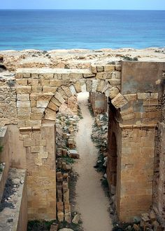 Partially collapsed western tunnel between de Amphitheatre's arena n de Hippodrome at Leptis Magna. De archway at de entrance to de tunnel in de foreground frames a path leading on de beach n de Mediterranean Sea. Ancient Ruins, Ancient Rome, East Africa, North Africa, Alexandria Egypt, Roman City, Ancient Architecture, Ancient Civilizations, Roman Empire