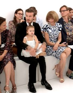 Harper Beckham steals the show as she she sits on her dad David Beckham's lap during her mom Victoria Beckham's runway show at New York Fashion Week.