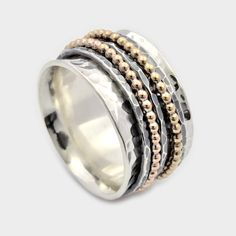 This five band spinner ring is an incredible addition to your everyday jewelry collection. The base of the ring features a concave design of hammered silver, wide enough for a man to wear yet perfect for a woman as well. The five spinning bands consist of alternating hammered silver and beaded gold bands. Each of the five spinning bands rotate individually around the base ring for an interesting and fun everyday ring.  Dimensions: Width: 12mm Weight: 13 grams  Here you can find our silver…