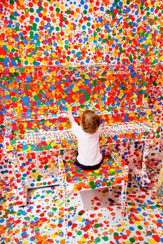 Yayoi Kusama's legendary installation, Obliteration Room, where thousands of children were given colorful stickers and unbridled freedom in a stark white room.