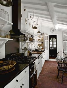 black and white galley kitchen, french vintage lights, brick floor, open shelving