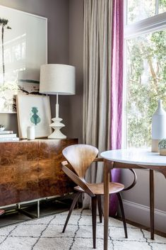 Love this pop of violet in this neutral living room nook. Those bentwood midcentury dining chairs are the stuff of dreams! See the rest of this modern and feminine redesign and total gut renovation of a historic San Francisco home on Architectural Digest.