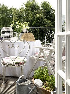My French taste is always white iron chairs for a lovely balcony setting......
