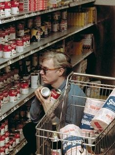 Andy Warhol looking at Campbell's soup cans in a supermarket near the Factory, his studio, in 1965. Campbell's Soup Cans (1962) displayed at Warhol's first single artist show, and became one his first and most iconic images.