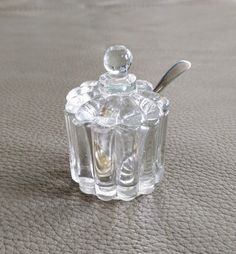Vintage salt cellar, ca. early 1950s. Unsigned. Includes bowl, lid, and spoon.  Clear pressed glass in a scalloped design, with a silver plated spoon. 2 1/2 tall, 1 5/8 diameter. Spoon is 2 1/2 long.  Can be used to serve salt, sugar, spices, etc.   Excellent vintage condition. No cracks or discoloration. Clean, bright, and ready to use.   Bought originally in Maine and owned by the same family for 60 years.   Shop with confidence! I will combine shipping, and I do accept retur...
