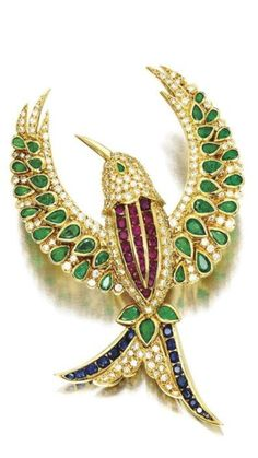 Gem-Set and Diamond 'Birds of Paradise' Brooch Clip by VAN CLEEF & ARPELS  Designed as a fleeting bird, set with circular-cut Diamonds, highlighted with pear-shaped Emerald eye and wings weighing approximately 1.20 carats in total, to the circular-cut Ruby and Sapphire details, mounted in yellow Gold, signed Van Cleef & Arpels and numbered, case stamped Van Cleef & Arpels.