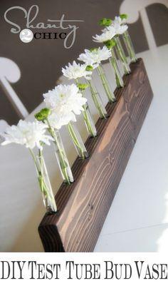 Selbst gemachte Blumenvase. Einfach Löcher in ein Holzbrett bohren und passende Reagenzgläser hineinstellen. Sieht toll aus.