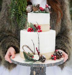gâteau de mariage d'hiver orné de pommes de pin et de brins d'arbre