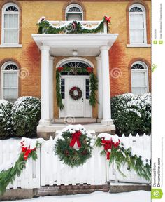 Historic brick home with pillared porch and Christmas decorations and fresh snow in Jacksonville, Oregon.