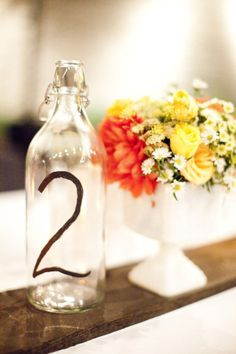 table number painted on a bottle. straightforward and simple! i'd make it a little prettier though...