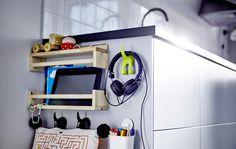 A lateral de um armário de cozinha alto com cestos e uma calha para uma área de lavandaria