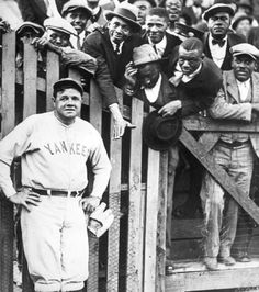 Babe Ruth  1925  Fans clamor to speak with Babe Ruth as he poses along the outfield fence.