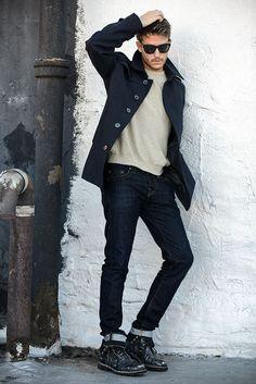 Shop this look on Lookastic: http://lookastic.com/men/looks/sunglasses-trenchcoat-crew-neck-sweater-jeans-boots/6415 — Black Sunglasses — Black Trenchcoat — Beige Crew-neck Sweater — Navy Jeans — Black Leather Boots
