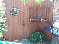 I built this privacy gate to my patio.  I used old shutters to make fake windows and shelves for small potted plants.