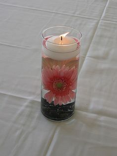This candle, for example, burns in water, atop rocks and pink gerber daisies. How creative! Give your guests some color! All it takes is finding some cheap, cylindrical glasses at your favorite discounter and asking for some extra gerber daisies.