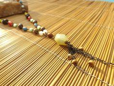 colar envelhecido,colorido feito com contas de vidro ,madeira,corrente e uma pedra verde clara no centro.