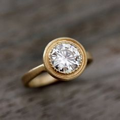 love unique rings!     moissanite & 14k yellow gold engagement ring, matte gold with textured bezel