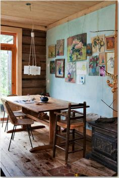 So many beautiful things here - wide floor boards, natural light, rustic table, wooden highchair, floral paintings and turquoise wall.