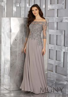 MGNY | Madeline Gardner, Evening Dress style 71621. Grey Chiffon Long Social Occasion Gown with Sparkly Crystal Beaded and Embroidered Off-the-Shoulder Long Sleeve ¾ Bodice. A-Line Style would look Stunning at a Fall or Winter Wedding. Colors Available: Teal Blue Green, Pewter Grey. Perfect for any Formal event including a Military Ball and Mother of the Bride.