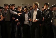 A group of Chechen men at a party, standing at the opposite end of the women.  In Chechnya, under strongman Ramzan Kadyrov, gender segregation is being enforced.