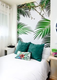 All-white bedroom with a tropical wallpaper headboard