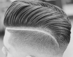 This is a classic low-mid razor faded pompadour that looks amazingly well done. A lot of barbering prowess went into making this cut happen.