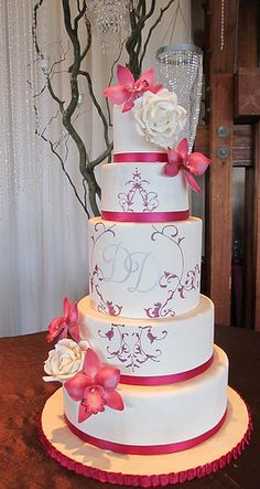 Hey, those are my initials! Lol. Fuschia. Here is a huge cake done in fuschia and white with sugar orchids, roses and handpainted detailing pulled from the wedding invitation.  Lemon cake with white chocolate buttercream and fresh raspberries