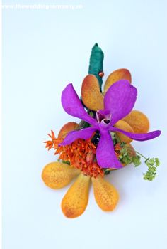 Love this multicolored boutonnière with purple and orange flowers