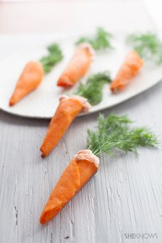 """""""Carrots"""" with salmon mousse! Crispy wafer cones are filled with a goat cheese salmon mousse and topped with a sprig of dill"""