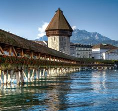 Lucerne, Switzerland.  Cross the wooden bridge, eat bavarian style food, walk the old city walls, take a cable car to Mount Pilatus.