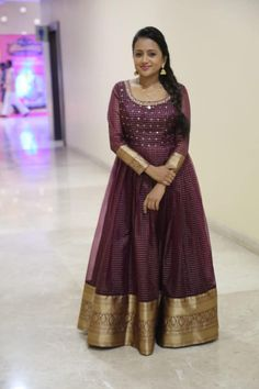 Beautiful anchor Suma in wine color floor length dress with full sleeves. Floor length dress with gold jari boarder and sleeves. She adorned with statement jumkhis. Girls Frock Design, Long Dress Design, Dress Neck Designs, Fancy Blouse Designs, Saree Blouse Designs, Half Saree Designs, Long Gown Dress, Sari Dress, Long Dresses