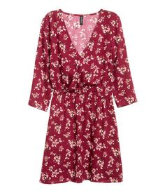 Burgundy/floral. Short dress in woven fabric with a wrap-front bodice. Concealed snap fastener at top, 3/4-length sleeves, and an elasticized seam at waist